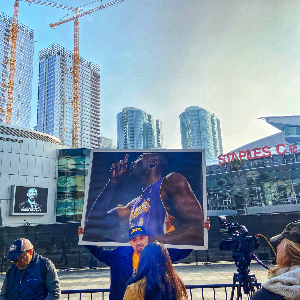 Picture outside the Staples Center of a fan holding a Kobe Bryant poster.